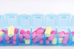 Закрыно вверх по капсуле и таблеткам в ежедневной коробке пилюльки Стоковые Фото