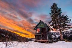 Закрытая лачуга лыжного курорта с изумительным восходом солнца во время зимы стоковая фотография rf