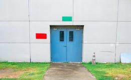 Закрытая голубая дверь с зеленым и красным текстовым полем на белых бетонной стене, траве и дорожке стоковое фото rf
