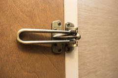 Закрытая и запертая коричневая деревянная дверь с медной латунью покрасила защелку стоковое фото