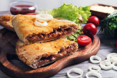 Закрытое calzone пиццы на светлой деревянной предпосылке Стоковая Фотография RF