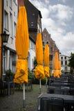 Закрытые желтые зонтики солнца в кафе улицы на ненастном лете d Стоковые Изображения