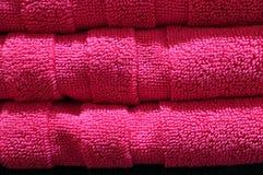 Закрытый вверх по текстуре аккуратно сложенного живого Fuchsia розового пушистого стога полотенец ванны Стоковая Фотография