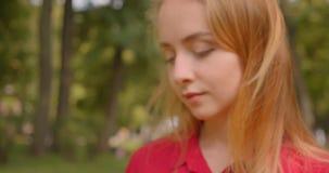 Закрытый портрет молодой блондинки с длинными волосами-красотки, которая пользуется телефоном, сидящим на траве в парке на улице акции видеоматериалы