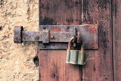 Закрытый старый ржавый железный замок и винтажный padlock на трескать и слезать выдержанную красную деревянную дверь стоковые изображения rf