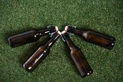 4 закрытых пивной бутылки лежа совместно на зеленой траве Стоковые Фото