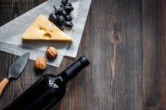 Закуска вина Сыр, гайки, виноградина на темном copyspace взгляд сверху предпосылки деревянного стола Стоковые Изображения RF