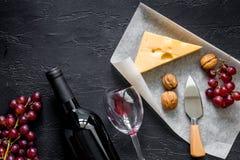 Закуска вина Сыр, гайки, виноградина на черном каменном copyspace взгляд сверху предпосылки таблицы Стоковое Изображение