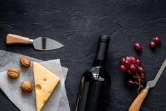 Закуска вина Сыр, гайки, виноградина на черном каменном copyspace взгляд сверху предпосылки таблицы Стоковое фото RF