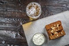 Закуска пива здравицы хлеба с чесноком, с соусом на доске для хранить покрыта с листом пергамента взгляд от Стоковые Изображения RF