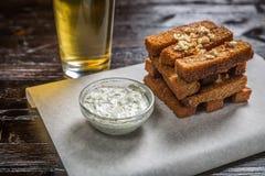 Закуска пива здравицы хлеба с чесноком, с соусом на доске для хранить покрыта с листом пергамента Стоковое фото RF