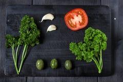 Закуска установленная на деревянную доску С оливками, петрушка, томат, чеснок Взгляд сверху Темная предпосылка стоковые изображения