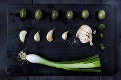 Закуска установленная на деревянную доску С оливками, петрушка, чеснок Взгляд сверху Темная предпосылка стоковые изображения rf