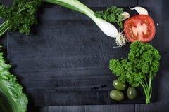 Закуска установленная на деревянную доску С оливками, петрушка, чеснок Взгляд сверху Темная предпосылка стоковое изображение rf