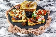 Закуска bruschetta Antipasti изысканная Сэндвич со смоквами и ветчиной ингредиенты для здоровой концепции еды стоковое изображение