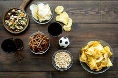 Закуски для смотреть футбол по телевизору наблюдать спортов Обломоки, гайки, сухари около пива и футбольный мяч на темное деревян стоковая фотография rf
