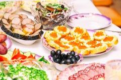 Закуски, плоды, сэндвичи, салаты, икра и отрезать на таблице праздника стоковое изображение rf