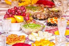 Закуски, плоды, сэндвичи, салаты, икра и отрезать на таблице праздника стоковое изображение