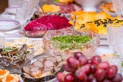 Закуски, плоды, сэндвичи, салаты, икра и отрезать на таблице праздника стоковые изображения rf