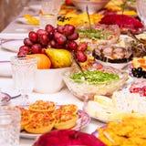 Закуски, плоды, сэндвичи, салаты, икра и отрезать на таблице праздника стоковая фотография