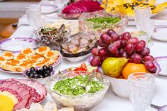 Закуски, плоды, сэндвичи, салаты, икра и отрезать на таблице праздника стоковое фото rf