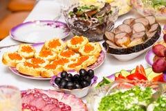 Закуски, плоды, сэндвичи, салаты, икра и отрезать на таблице праздника стоковое фото