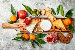 Закуски ставят на обсуждение с закусками antipasti Доска разнообразия сыра над серой конкретной предпосылкой Взгляд сверху, плоск стоковая фотография