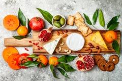 Закуски ставят на обсуждение с закусками antipasti Доска разнообразия сыра над серой конкретной предпосылкой Взгляд сверху, плоск стоковые фото