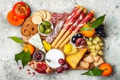 Закуски ставят на обсуждение с закусками antipasti Разнообразие сыра и мяса всходит на борт над серой конкретной предпосылкой Взг стоковые фото