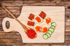 Закуски с красной икрой на деревянной предпосылке Стоковые Изображения