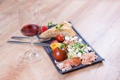 Закуски с красным вином на черном шифере всходят на борт над деревянной предпосылкой Деликатес и простая еда, хлеб, сыр, томаты и Стоковое Фото