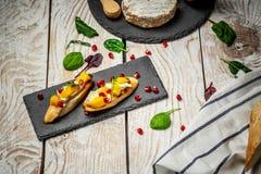 Закуски Antipasti для вина Brushetta с манго, сыром камамбера и гранатовым деревом служило на доске сланца, деревенском деревянно стоковые изображения