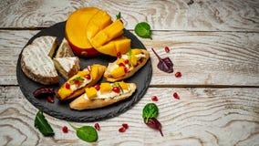 Закуски Antipasti Brushetta с манго, сыром камамбера и гранатовым деревом служило на доске сланца, деревенском деревянном столе с стоковая фотография