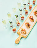 Закуски, brushettas, съемки гаспачо, десерты, шампанское над пастельной голубой предпосылкой Стоковая Фотография