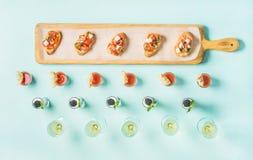 Закуски, brushettas, съемки гаспачо, десерты, шампанское над пастельной голубой предпосылкой стоковая фотография rf