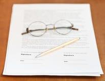 Заключите контракт, золотые ручка и eyeglasses на таблице стоковые изображения
