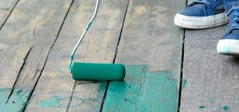 Заключите контракт художника крася пол с зеленой краской стоковое изображение rf