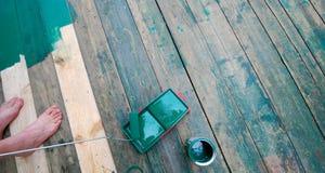 Заключите контракт художника крася пол с зеленой краской стоковые фотографии rf