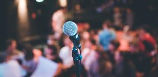Зала события: Закройте вверх стойки микрофона, мест с аудиторией в расплывчатой предпосылке стоковое изображение