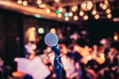 Зала события: Закройте вверх стойки микрофона, мест с аудиторией в расплывчатой предпосылке стоковая фотография