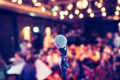 Зала события: Закройте вверх стойки микрофона, мест с аудиторией в расплывчатой предпосылке стоковые фотографии rf