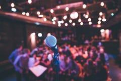Зала события: Закройте вверх стойки микрофона, мест с аудиторией в расплывчатой предпосылке стоковые изображения rf