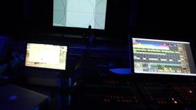 Зала театра в подготовке к шоу Профессиональное зарево оборудования и ноутбуков на таблице в темноте залы театра дальше акции видеоматериалы