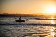 ЗАЛИВ БАЙРОНА, NSW, АВСТРАЛИЯ - заниматься серфингом на заходе солнца Стоковые Фото