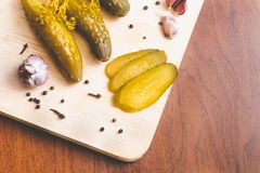 Замаринованные зеленые огурцы, чеснок и специи на деревянной доске стоковая фотография rf