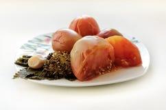 Замаринованные томаты с листьями смородины и укропа на плите Стоковое фото RF