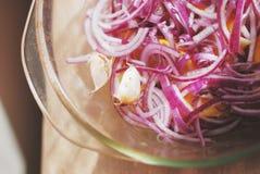 Замаринованный красный лук, грубо прерванный, с лимоном и чесноком в стеклянном блюде, взгляд сверху Стоковые Фото