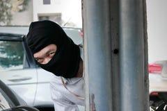 Замаскированный похититель пряча за поляком перед ограблением Концепция преступника угонщика Стоковая Фотография RF
