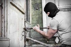 Замаскированный разбойник ломает дверь замка в доме Стоковые Фото