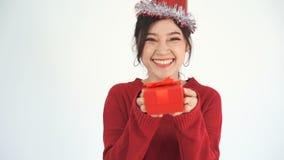 Замедление счастливой женщины с шляпой и держать красную подарочную коробку рождества в жесте давать видеоматериал